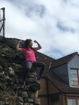 A pre-teen girl sits on a wall, flexing muscles